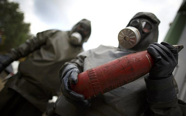 Employees in protective gear holding a dummy grenade during a demonstration at a chemical weapons disposal facility in Munster, northern Germany, October 30, 2013 (AFP PHOTO/ Phillip Guelland)