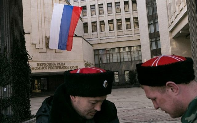 A Russian and a Crimean Cossacks volunteer stand guard in front of Crimea's regional parliament building where a Russia flag is floating, in Simferopol, on March 14, 2014 (Daniel Leal Olivas / AFP)