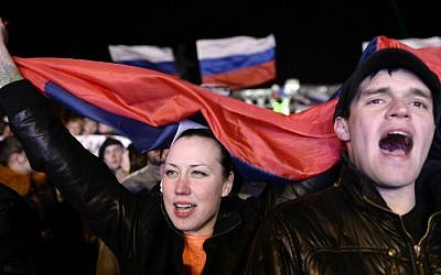 People sing the Russian national anthem as they celebrate in Simferopol's Lenin Square on March 16, 2014 after exit polls showed a huge majority of voters in Ukraine's Crimea region supported union with Russia. (photo credit: AFP photo / Dimitar Dilkoff)