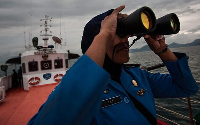 A member of Indonesia's National Search and Rescue looks over horizon during a search in the Andaman sea area around northern tip of Indonesia's Sumatra island for the missing Malaysian Airlines flight MH370 on March 17, 2014. (photo credit:AFP/ CHAIDEER MAHYUDDIN)