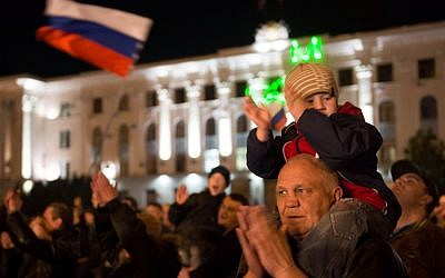 A young boy sits on the shoulders of an elderly man at a parade in the center of the Crimean city of Simferopol on March 21, 2014, after Russia's upper house of parliament unanimously voted to ratify the treaty incorporating Crimea into Russian territory. (photo credit: AFP/ Dmitry Serebryakov)
