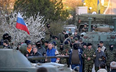 Pro-Russian militiamen cordon off as Russian soldiers storm the Ukrainian military airbase in Belbek near the Crimean city of Sevastopol on Saturday, March 22, 2014 (photo credit: AFP/Viktor Drachev)
