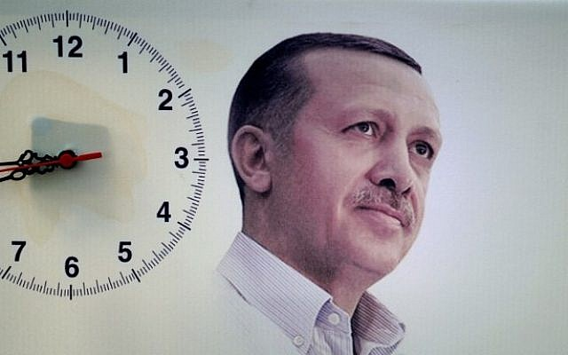 A poster showing Turkish Prime Minister Recep Tayyip Erdogan is seen next to a hanging clock during a rally of the Justice and Development Party (AKP) in the Maltepe district at the Asia side of Istanbul on Saturday, March 29, 2014 (photo credit: AFP/Ozan Kose)