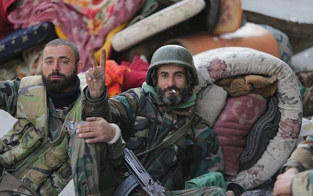 """A pro-government forces member flashes the """"V-sign"""" for victory next to a comrade in the main square of the Syrian town of Yabrud on March 16, 2014 after they seized full control of the rebel bastion in the strategic Qalamun region near the Lebanese border (photo credit: AFP/Joseph Eid)"""