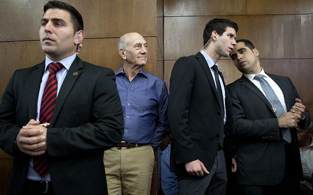 Former prime minister Ehud Olmert (C) waits in the Tel Aviv Destrict Court ahead of the reading of the verdict in the Holyland case, Monday, March 31, 2014 (photo credit: AFP/POOL/Dan Balilty)