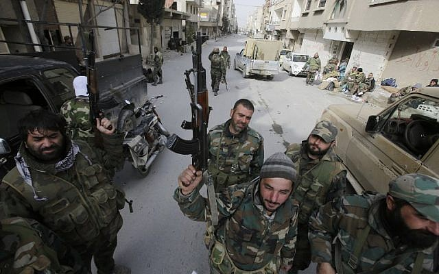 Pro-government forces stand on a street in the Syrian town of Yabroud on March 16, 2014 after they seized full control of the rebel bastion in the strategic Qalamun region near the Lebanese border. (photo credit: Topshots/AFP/Joseph Eid)