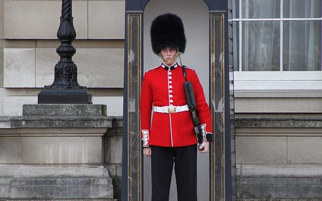 A guard outside London's Buckingham Palace (photo credit: CC BY-SA CatholicYouthWork.com/Flickr)