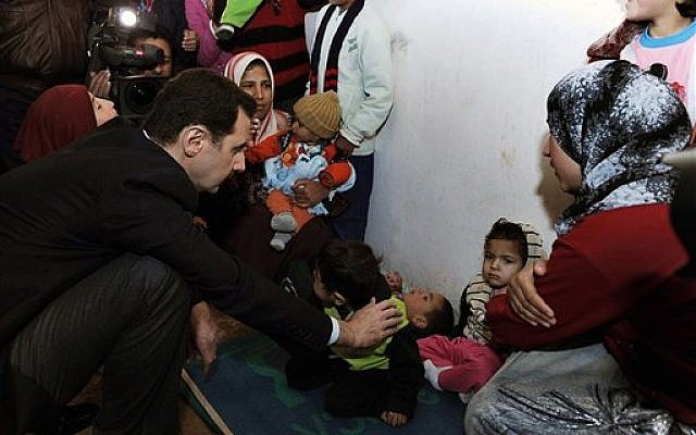 In this photo released on the official Facebook page of Syrian Presidency, Syrian president Bashar Assad, center left, visits a shelter of internally displaced people in the Damascus suburb of Adra, Syria, Wednesday, March 12, 2014.  (photo credit: AP)