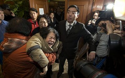 A relative of one of the Chinese passengers aboard Malaysia Airlines flight MH370 collapses in grief in Beijing, China, after being told that satellite data indicates the plane crashed into the Indian Ocean, Monday, March 24, 2014. (photo credit: AP/Ng Han Guan)