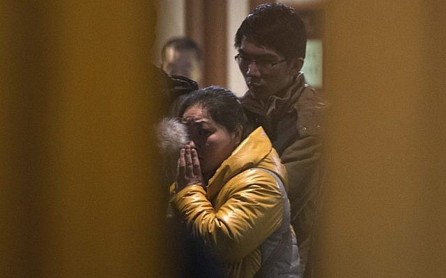 A Chinese relative of passengers aboard a missing Malaysia Airlines plane looks out from a hotel room for relatives or friends of passengers aboard the missing airplane, in Beijing, China Monday, March 10, 2014. (photo credit: AP Photo/Andy Wong)
