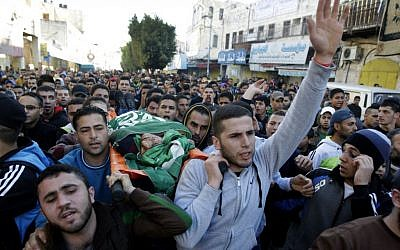 Palestinians carry the body of Hamas terror suspect Hamza Abu el-Hija, who was killed in a raid by Israeli troops, during his funeral procession, in the West Bank refugee camp of Jenin, Saturday, March 22, 2014. (photo credit: AP Photo/Mohammed Ballas)