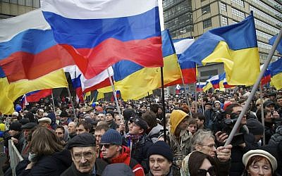 Demonstrators hold Russian and Ukrainian flags during a massive rally to oppose president Vladimir Putin's policies in Ukraine, in Moscow, Saturday, March 15, 2014. (photo credit: AP/Alexander Zemlianichenko)
