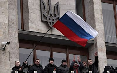 Pro-Russia demonstrators holding a Russian flag, with the Ukrainian emblem in the background, stand on the balcony of the regional administrative building after storming it in Donetsk, Ukraine, Wednesday, March 5, 2014. (photo credit: AP Photo/Sergei Chuzavkov)