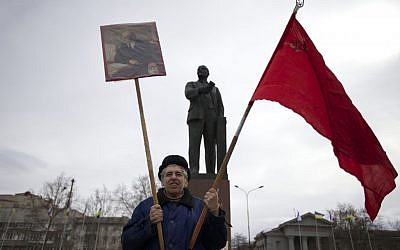 A local Communist party supporter holds Soviet flag and portrait of Soviet founder Vladimir Lenin as he stands next to Lenin's statue at a square in downtown Simferopol, Ukraine. (photo credit: AP Photo/Ivan Sekretarev)