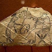 """A limestone with pigment shows a scene of a cat and mouse, in which animals perform human tasks, is displayed as part of the exhibit """"Soulful Creatures: Animal Mummies in Ancient Egypt,"""" at the Orange County's Bowers Museum in Santa Ana, Calif. (photo credit: AP/Damian Dovarganes)"""