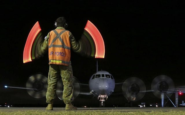 A ground crewman guides a RAAF AP-3C Orion along the tarmac as it returns from the search for missing Malaysia Airlines Flight MH370 in Perth, Australia, Sunday, March 30, 2014. (photo credit: AP/Rob Griffith)