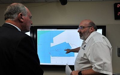 Mike Barton, rescue coordination chief, right, shows Australia's Deputy Prime Minister, Warren Truss, the map of the Indian Ocean search areas at the rescue coordination center of Australian Maritime Safety Authority in Canberra, Sunday, March 23, 2014. (photo credit: AP Photo/Graham Tidy, Pool)