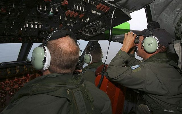 Flight Engineer Ron Day, right, on board a Royal Australian Air Force AP-3C Orion, searches for the missing Malaysia Airlines Flight 370 in the southern Indian Ocean on Wednesday, March 26. (photo credit: AP/Paul Kane, Pool)