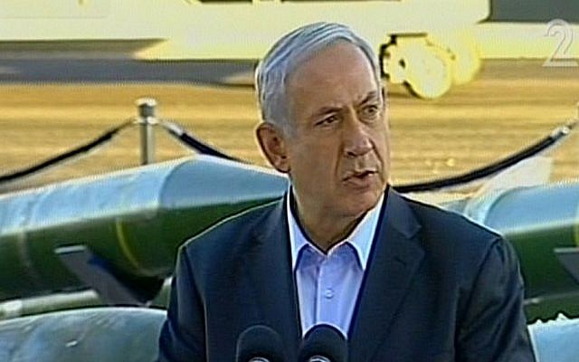 Prime Minister Benjamin Netanyahu speaks at an Israel naval base in the southern port city of Eilat on March 10, 2014. In the background, weapons seized on board the Klos-C can be seen on display. (screen capture, Channel 2)