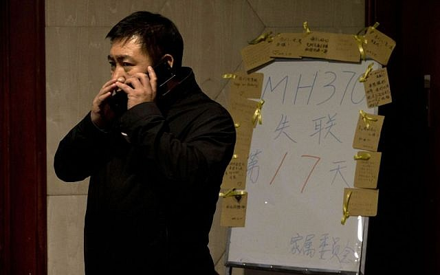 """A man whispers on a cellphone near a board which reads """"MH370 missing day 17"""" at a room reserved for relatives of Chinese passengers aboard the missing Malaysia Airlines jet in Beijing, China, Monday, March 24, 2014. (photo credit: AP/Ng Han Guan)"""