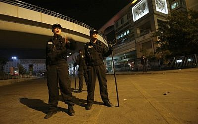Policemen guard outside a railway station after an attack by knife wielding men left some 27 people dead in Kunming, in southwestern China's Yunnan province, Saturday March 1, 2014 (photo credit: AP)