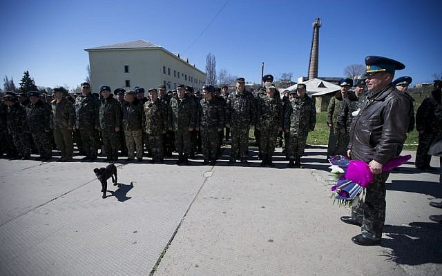 Colonel Yuly Mamchur, right, holds flowers as other Ukrainian airmen line up to greet their comrades who arrived to celebrate their wedding at the Belbek airbase outside Sevastopol, Crimea, on Saturday, March 22, 2014. (photo credit:  AP Photo/Ivan Sekretarev)