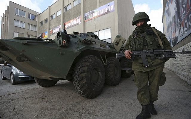 A soldier in an unmarked uniform stands guard at an APC outside the Ukrainian Military Prosecutor's Office in Simferopol, Crimea, Thursday, March 20, 2014. (photo credit: AP/Maxin Vetrov)