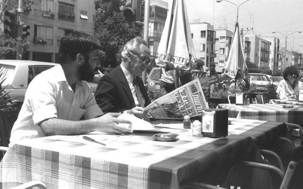 Shimon Peres reads a newspaper at a Tel Aviv cafe (photo credit: GPO)