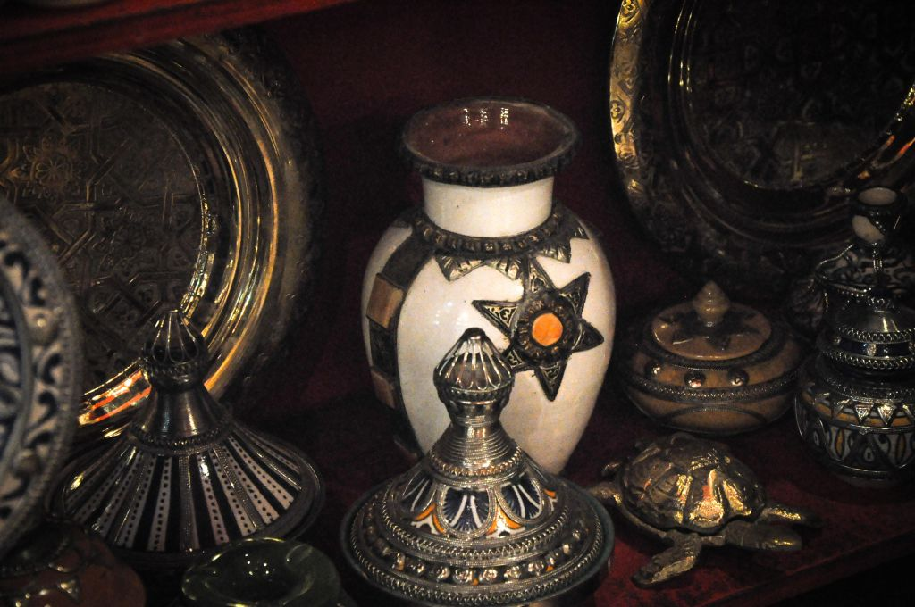 Jewelry and silver shops in Fez's medina display traditional tagine pots (front, center), which are placed in the fire to cook the Moroccan stew, often made with lamb, vegetables, fruit, and spices. Shops in Fez also have a variety of old and new Judaica, such as the vase pictured here.