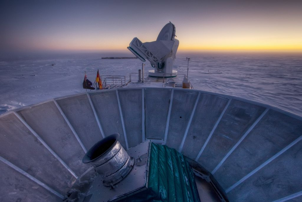 """In this 2007 photo provided by Steffen Richter, the sun sets behind the BICEP2 telescope, foreground, and the South Pole Telescope in Antarctica. In the faint glowing remains of the Big Bang, scientists found """"smoking gun"""" evidence that the universe began with a split-second of astonishingly rapid growth from a seed far smaller than an atom. To find a pattern of polarization in the faint light left over from the Big Bang, astronomers scanned about 2 percent of the sky for three years with the BICEP2 at the south pole, chosen for its very dry air to aid in the observations, said the leader of the collaboration, John Kovac of Harvard. (photo credit: AP Photo/Steffen Richter)"""