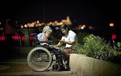 A Filipino caretaker at a promenade in Tel Aviv. (Photo credit: Moshe Shai/FLASH90)
