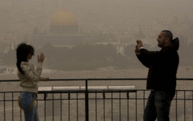 During a sandstorm, a couple stand on the Mount of Olives over looking the walls of the Old City of Jerusalem and the Dome of the Rock, on April 1, 2013. (photo credit: Yonatan Sindel/Flash90)