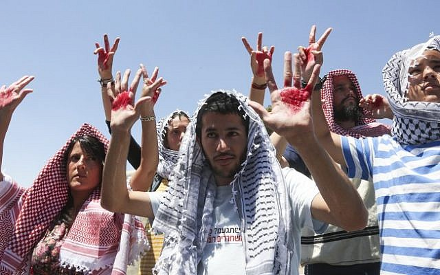 Israelis wearing keffiyehs hold up hands covered in fake blood to protest the release of Palestinian prisoners near the prime minister's office, July 28, 2013 (photo credit: Flash90)