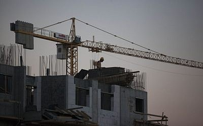 Laborers work at a housing construction site in the  Har Homa neighborhood in southeast Jerusalem on October 27, 2013 (photo credit: Flash90)