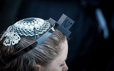 A Women of the Wall member dons a kippa and tefillin, Jewish ritual garb traditionally reserved for men (Flash90)