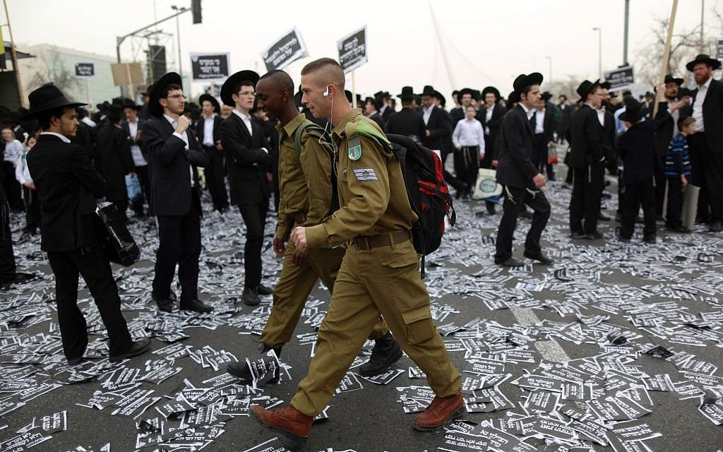 IDF soldiers walk by ultra-Orthodox Jews preparing for a massive protest against plans to introduce compulsory military service, March 2, 2014  (Yonatan Sindel/FLASH90)