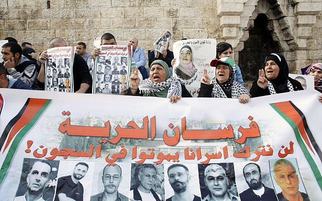 Palestinian protesters hold posters and banners with portraits of Palestinians jailed in Israeli prisons on Saturday, March 8, 2014, during a demonstration calling for their release at the Damascus Gate in Jerusalem's Old City (photo credit: Sliman Khader/Flash90)
