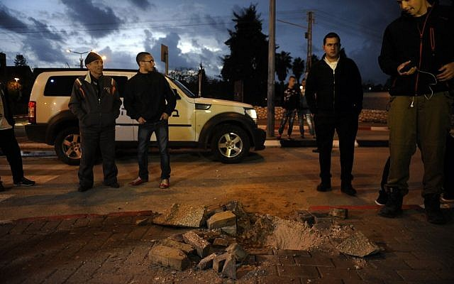 Israelis stand near a hole caused by a rocket fired from the Gaza strip into the southern city of Sderot on Wednesday, March 12, 2014 (photo credit: Flash90)