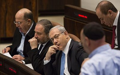 Defense Minister Moshe Ya'alon (L), Foreign Minister Avigdor Liberman (C) and Prime Minister Benjamin Netanyahu seen in the plenum hall during a vote on the Draft law. March 12, 2014. (Photo credit: Flash 90)