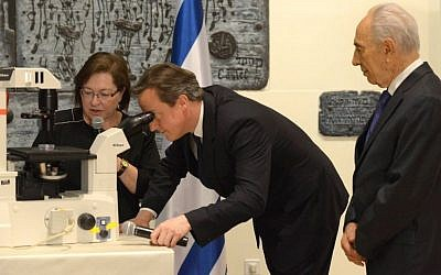 British Prime Minister David Cameron looks through a microscope at half-developed embryonic stem cells as Dr. Sharona Even-Ram of the Hadassah Medical Center tells him and President Shimon Peres about how the cells can be used to treat Parkinson's disease during a research exhibition at Beit HaNassi Wednesday evening. (Photo credit: Mark Neiman/GPO)