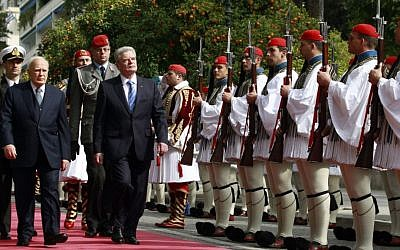 Greek President Karolos Papoulias, left, and his German counterpart Joachim Gauck, right, inspect a presidential guard during an official welcome ceremony outside the presidential palace, in Athens , on Thursday, March 6, 2014. (AP Photo/Kostas Tsironis)