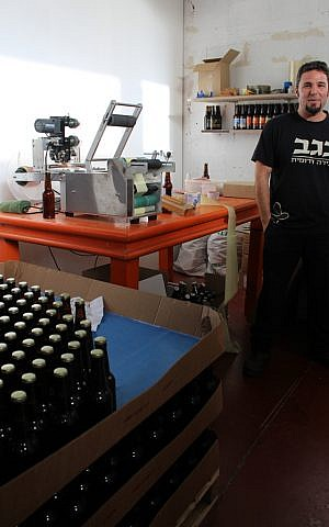 Tomer Ronen, one of the brewers at the Negev Brewery, uses a machine to speed up the labeling process for the thousands of bottles the brewery produces each month. (The Times of Israel/Rebecca McKinsey)
