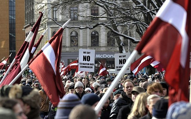 People carry Latvian flags as they march to the Freedom Monument to commemorate World War II veterans who fought in Waffen SS divisions, in Riga, Latvia, Sunday, March 16, 2014. (photo credit: AP/Roman Kosarov, F64 Photo Agency)