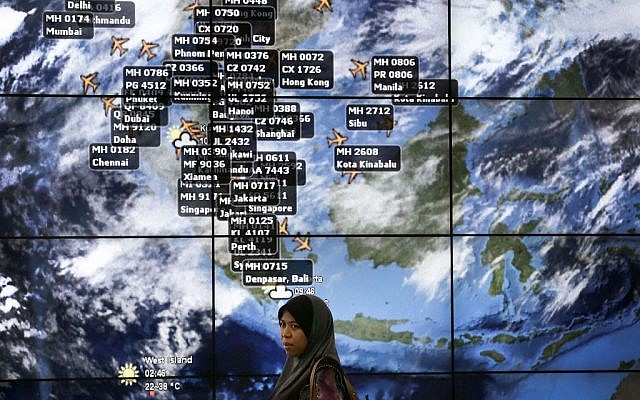 A woman stands in front of a display showing flight locations at the Kuala Lumpur International Airport, Sunday, March 16, 2014 in Sepang, Malaysia. (photo credit:AP/Wong Maye-E)