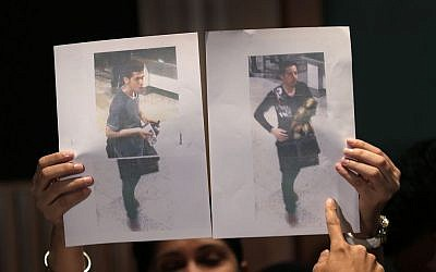 Pictures of two Iranian men who boarded the now missing Malaysia Airlines jet MH370 with stolen passports, held up by a Malaysian policewoman during a press conference, on Tuesday, March 11, 2014 in Sepang, Malaysia. (photo credit: AP Photo/Wong Maye-E)