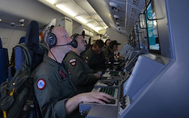 In this photo provided by the US Navy, crew members on board an aircraft P-8A Poseidon assist in search and rescue operations for Malaysia Airlines flight MH370 in the Indian Ocean on Sunday, March 16, 2014. (photo credit: AP/US Navy, Eric A. Pastor)