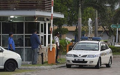 A police car comes out of a main gate of the missing Malaysia Airlines pilot Zaharie Ahmad Shah's house in Shah Alam, outside Kuala Lumpur, Malaysia, on Saturday, March 15, 2014. (photo credit: AP Photo)
