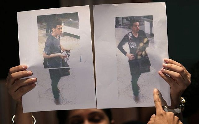 Pictures of the two men, a 19-year old Iranian, identified by Malaysian police as Pouria Nour Mohammad Mehrdad, left, and the man on the right, his identity still not released, who boarded the now missing Malaysia Airlines jet MH370 with stolen passports, is held up by a Malaysian policewoman during a press conference, Tuesday, March 11, 2014.(AP Photo/Wong Maye-E)