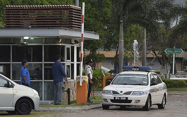 A police car comes out of a main gate of the missing Malaysia Airlines pilot Zaharie Ahmad Shah's house in Shah Alam, outside Kuala Lumpur, Malaysia, Saturday, March 15, 2014. (photo credit: AP)