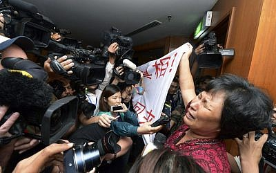 "A Chinese relative of passengers aboard a missing Malaysia Airlines plane cries as she holds a banner in front of journalists reading 'We are against the Malaysian government for hiding the truth and delaying the rescue. Release our families unconditionally!"" at a hotel in Sepang, Malaysia, Wednesday, March 19, 2014. Malaysian authorities examined new radar data from Thailand that could potentially give clues on how to retrace the course of the Malaysia Airlines plane that vanished early March 8 with 239 people aboard en route from Kuala Lumpur to Beijing. Twenty-six countries are looking for the aircraft as relatives anxiously await news. (photo credit: AP Photo)"